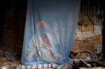 Hindu holy man, or sadhu, sits inside mosquito net at his ashram at Pashupatinath Temple in Kathmandu