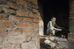 Hindu holy man, or sadhu, sits near fire to dry ashes smeared on his body at his ashram in Pashupatinath Temple in Kathmandu