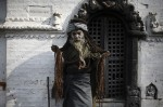 A Hindu holy man, or sadhu, displays his hair to the devotees passing by, at the premises of Pashupatinath Temple in Kathmandu