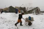 Afghan boy rolls a cart with cans of water after a snowfall in a refugee camp in Kabul, Afghanistan, February 17, 2012. In many parts of Afghanistan, no running water. (Ahmad Jamshid  Associated Press)