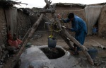 Villager taking on water in the well in the slums in Islamabad, July 14, 2011. (KMChaudary Associated Press)