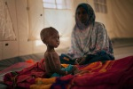22-year-old Fatime Abd Rahmane sits next to his 23-month-old daughter Kaltouma Abdoulaye, who is undergoing treatment for acute malnutrition in intensive care at a clinic in Mondo, April 19, 2012.