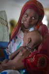 A woman holds in her arms her two-year child named Hawa Moussa, who is suffering from malnutrition, the Ngurah Rai, Chad, April 18, 2012.