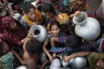 People are pushed into the queue for water on the outskirts of Dhaka. (ANDREW BIRAJ REUTERS)