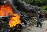 Striking miners puts a burning tire barricade on Highway A-66 in Campomanes, Spain. (ELOY ALONSO REUTERS)