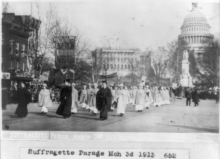 A fragment of the parade. On the sign says Home and Homework, which describes the status of women at the time.