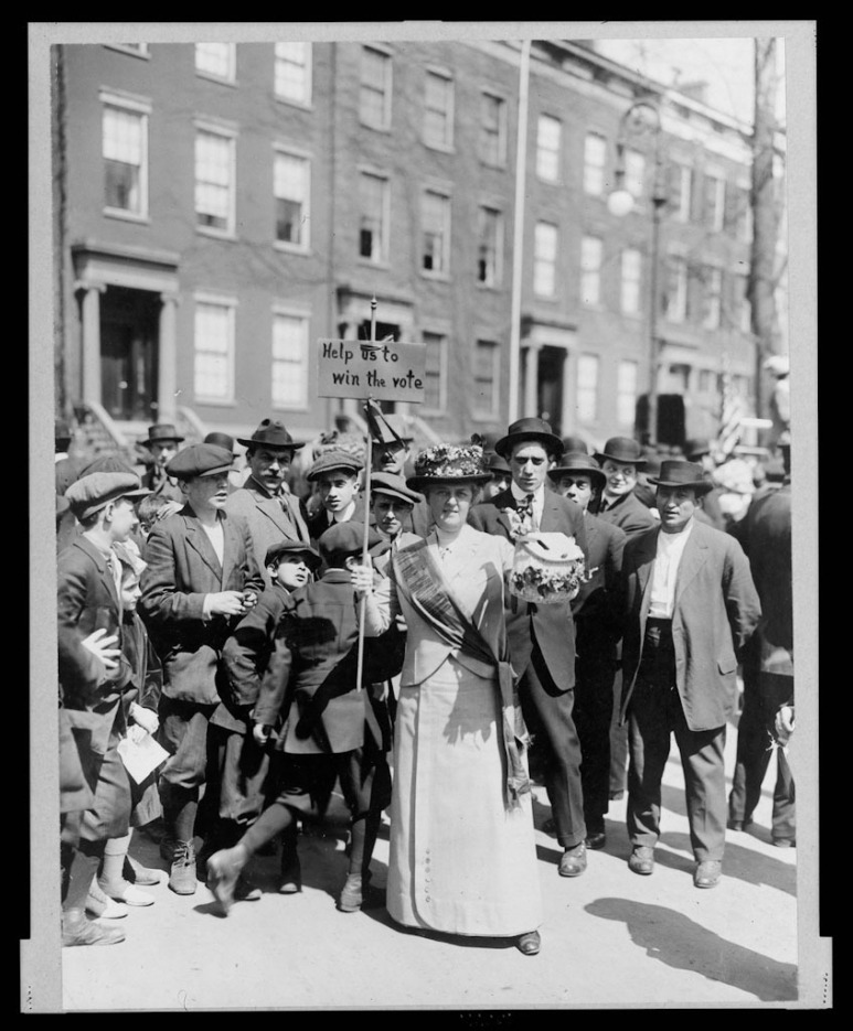 Ms. Suffern with homemade signs at the parade March 3, 1913
