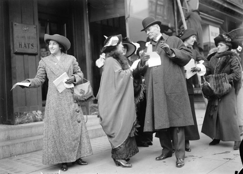 Suffragettes handing out leaflets about the upcoming parade.